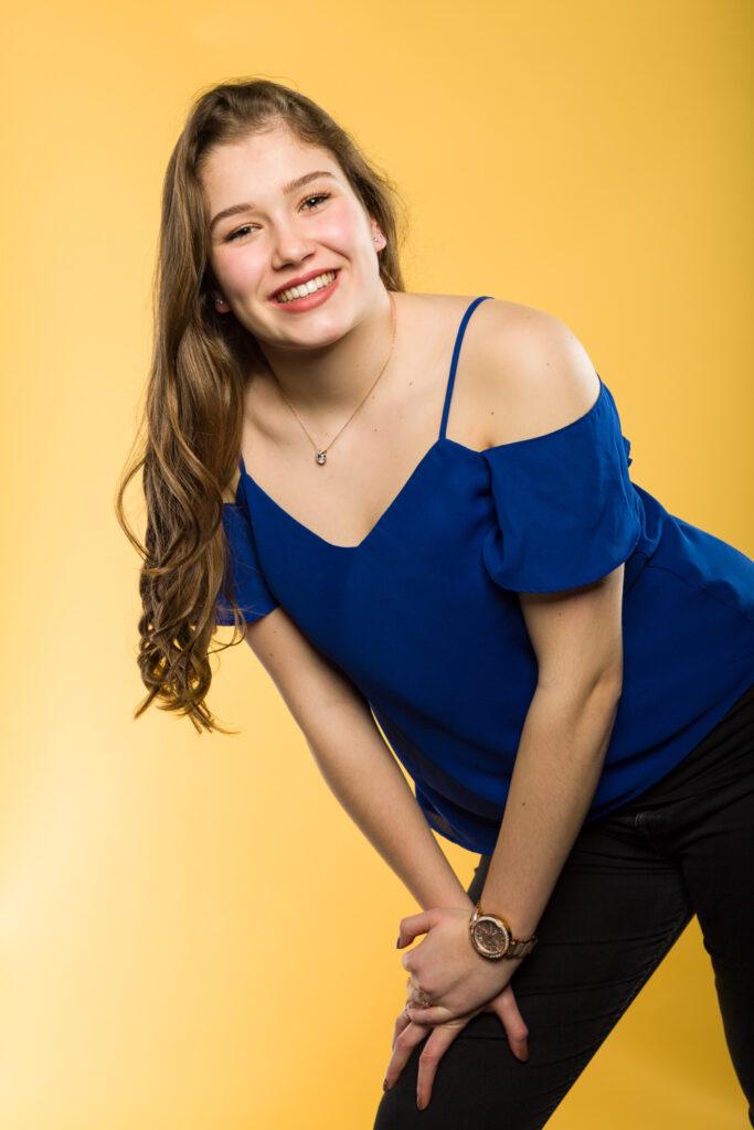 Carmen in blauwe kleding voor een geel scherm